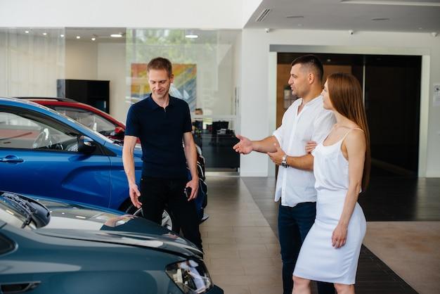 若いカップルがディーラーで新車を選び、ディーラーの代表者に相談します。中古車販売。夢の実現。