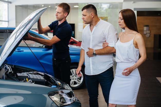 Молодая пара выбирает новую машину в автосалоне и консультируется с представителем автосалона.