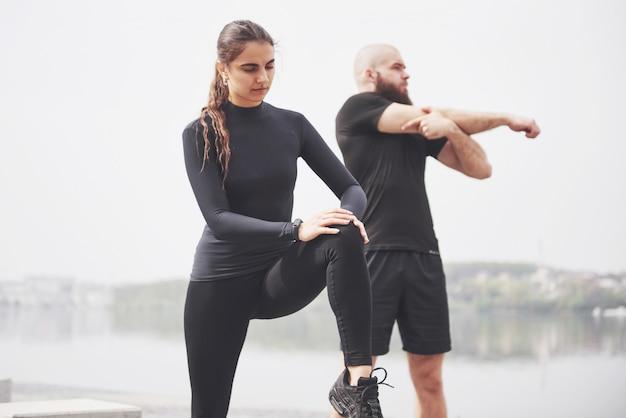 若いカップルは、朝、戸外でスポーツを楽しんでいます。運動前にウォームアップ