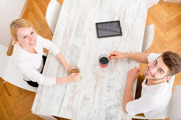 Молодая пара флиртует и пьет кофе.