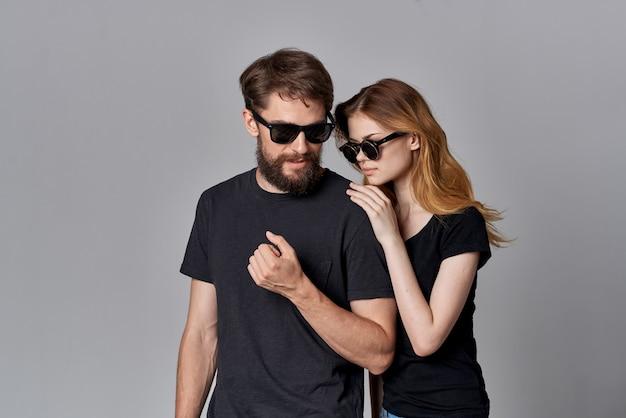 サングラスの明るい背景を身に着けている若いカップルの友情コミュニケーションロマンス
