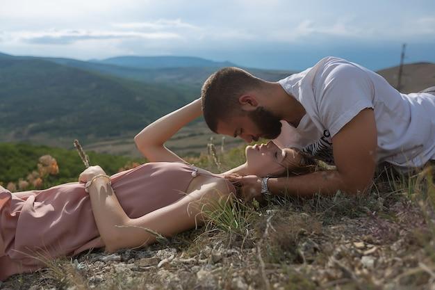 Молодая пара, парень и женщина лежат на траве и смотрят друг на друга на фоне высоких гор и голубого неба. красивая природа.