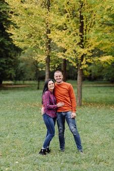 秋の公園で楽しんでいる若いカップル。デート、魅力的
