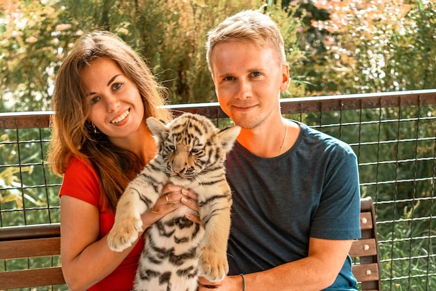 若いカップルが小さなトラの子を抱きます