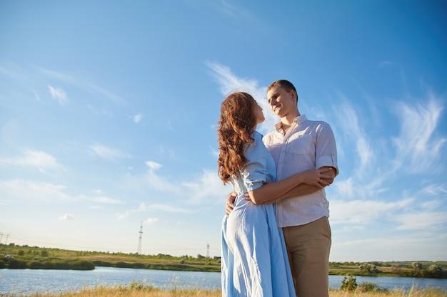 Молодая пара обнимается в поле на фоне реки или озера и радуется жизни