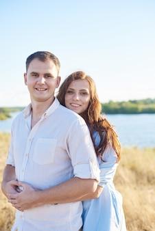 Молодая пара обнимается на пшеничном поле, смеется и радуется жизни. концепция любви и правильных отношений без насилия.