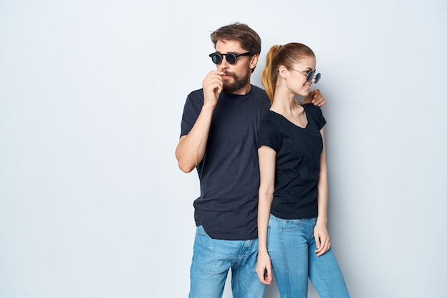 밝은 배경에서 포즈를 취하는 검은색 티셔츠 선글라스를 쓴 젊은 부부