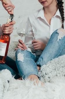 청바지와 흰색 셔츠를 입은 젊은 부부가 침대에서 장미 와인 한 병을 엽니다