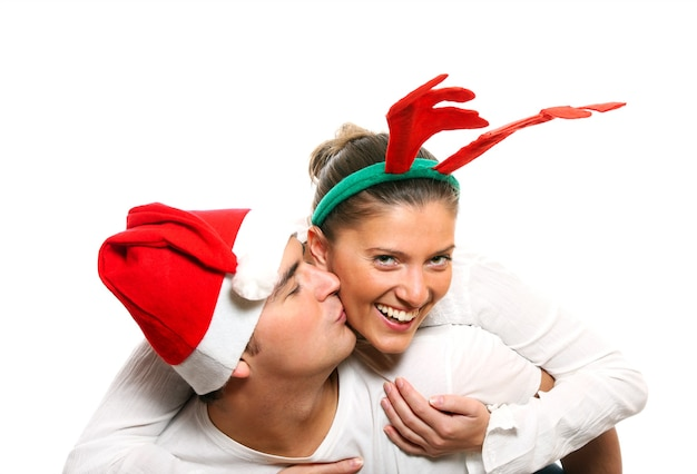 白い背景の上で遊ぶクリスマスの衣装を着た若いカップル