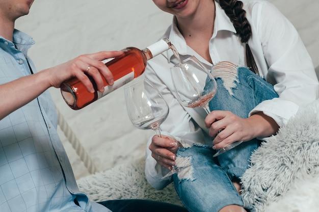 청바지와 셔츠를 입은 젊은 부부가 병에서 장미 와인을 침대에 앉아 있는 안경에 붓는다