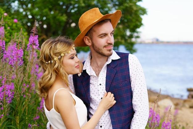 男と女を愛する若いカップルが自然の中を歩いている女の子は美しいブロンドです...