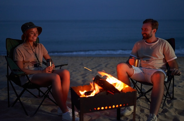 愛する若いカップルが火のそばの折りたたみ椅子に座って、夜に海岸でお茶を飲んでいます。