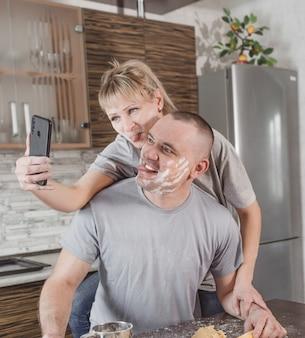 밀가루가 묻은 부엌에서 사랑에 빠진 젊은 부부가 셀카를 찍는다. 그는 얼굴을 만들고 혀를 보여줍니다.