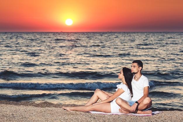 Молодая влюбленная пара отдыхает и наслаждается восходом солнца на берегу моря.