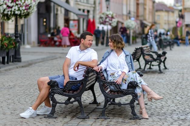 Молодая влюбленная пара сидит на скамейке. парень и девушка смотрят друг другу в глаза. первое свидание.