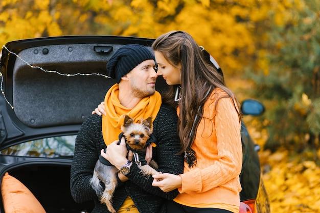 愛の若いカップルが黒い車の開いたトランクに座っています