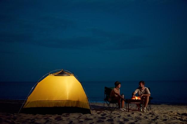 愛する若いカップルが火のそばのテントの近くの折りたたみ椅子に座って、ビーチで話を楽しんでいます