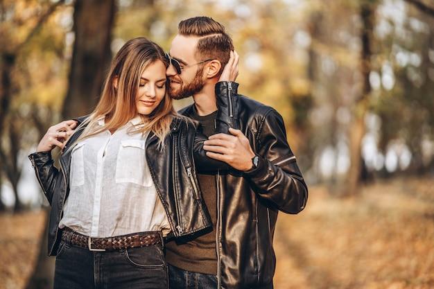 Молодая пара в любви, прогулки в парке осенью в солнечный день. мужчина нежно обнимает женщину. любовная история