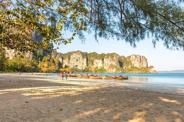 愛する若いカップルがボートを背景に海の砂浜を歩きます。