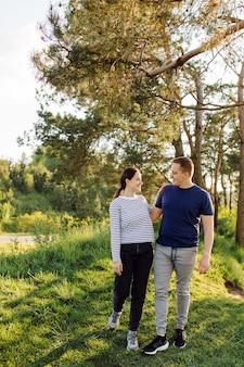 恋をしている若いカップルが森の中を歩き、一緒に楽しい時間を過ごします