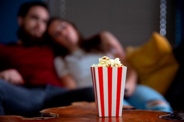 Молодая влюбленная пара смотрит телевизор ночью, романтическое свидание, лежа на диване, ест попкорн
