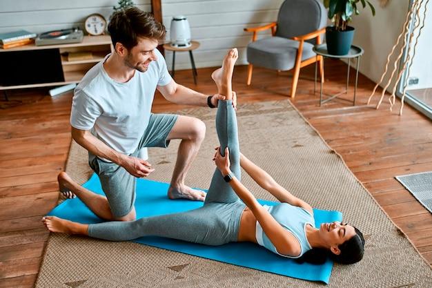 Молодая пара в спортивной одежде делает зарядку на циновках дома в светлой уютной гостиной. здоровый образ жизни, спорт, йога, фитнес.