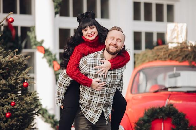 Молодая пара в теплой одежде вместе веселится в новогодней атмосфере на улице