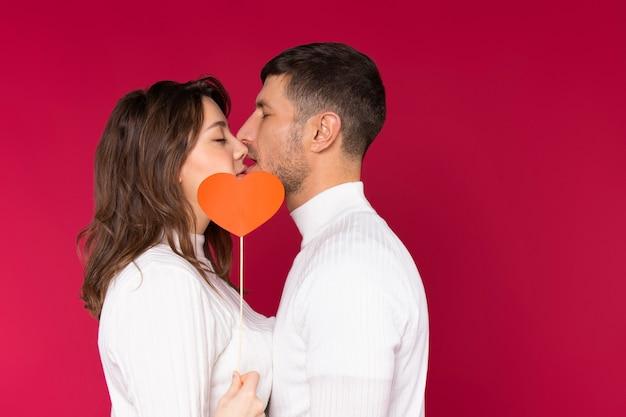 Молодая пара в белых свитерах прикрывает свой страстный поцелуй красным сердцем на красном фоне.