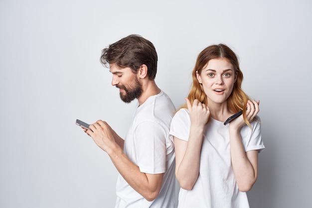 그들의 손 스튜디오 라이프 스타일에 전화와 흰색 티셔츠에 젊은 부부. 고품질 사진