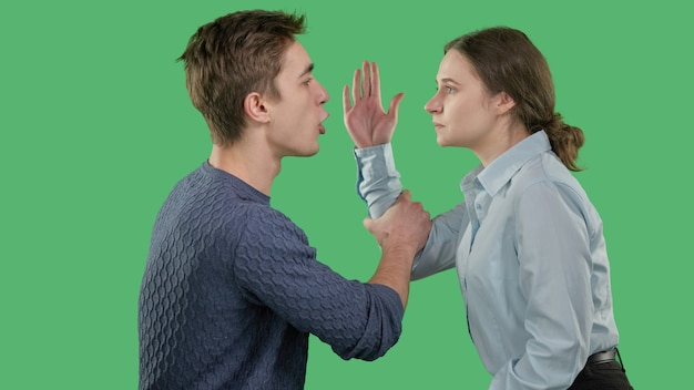 젊은 부부가 싸우고 있으며, 스캔들 동안 소녀는 젊은 남자의 얼굴을 때리려고 했습니다.
