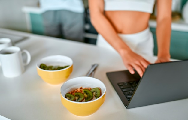 젊은 부부는 부엌에서 아침을 먹고있다. 건강한 음식, 체중 감소. 흰 속옷을 입은 소녀가 노트북을 사용합니다.