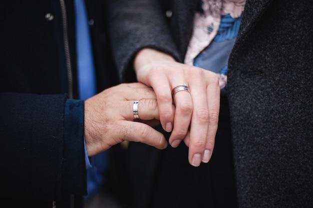 젊은 부부는 신부와 신랑의 손가락에 손을 잡고 결혼 반지를 닫습니다