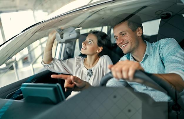 젊은 부부가 새 차에 앉아 그것을 검사하고 있습니다. 자동차 판매점에서 자동차를 사고 렌트합니다.