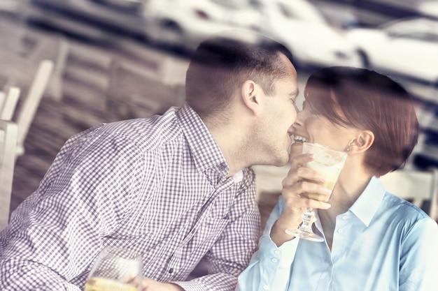 창문을 통해 찍은 레스토랑에서 키스하는 젊은 부부