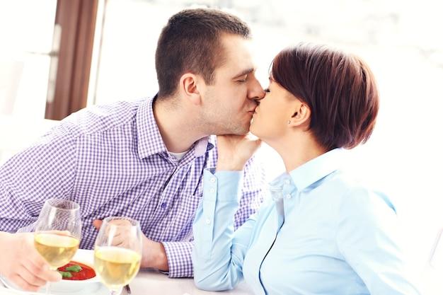 Молодая пара целуется в ресторане