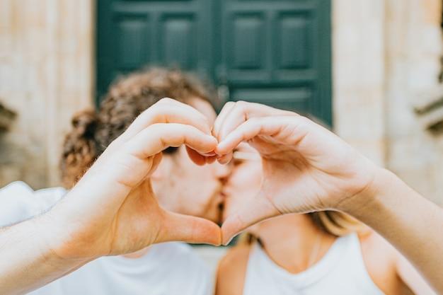 若いカップルが手でハートマークを作り、お互いにキス
