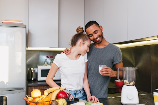 キッチンで朝食を作る若いカップル。 tシャツを着た男女が抱き合って、一緒に料理をし、幸せそうな顔で抱き合うカップル