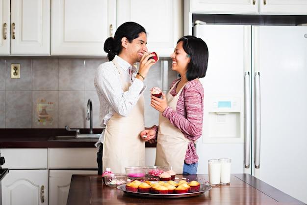 Молодая пара делает кексы на день святого валентина, играет и смеется
