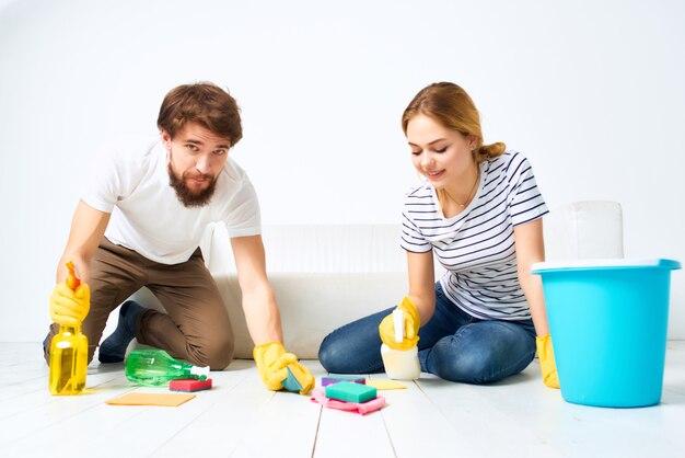 サービスのアパート提供のソファ掃除の近くの若いカップル。高品質の写真