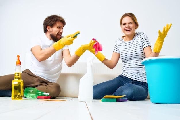 ソファの掃除の近くの若いカップルは明るい背景を供給します