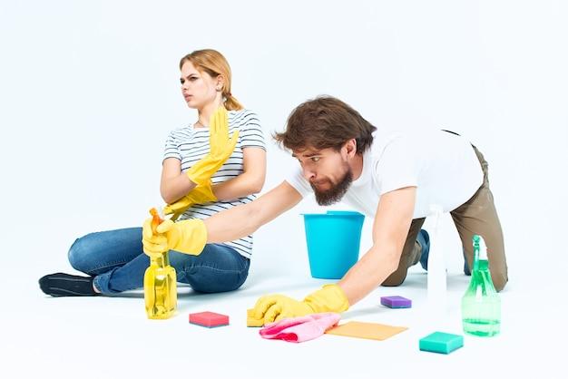 밝은 배경을 청소하는 소파실 근처의 젊은 부부