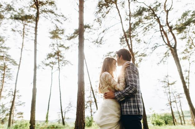 소나무 숲에서 산책하는 신부의 젊은 부부