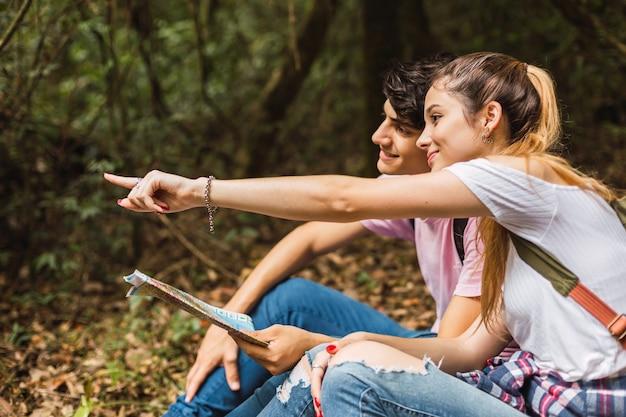 道を探している地図を持つハイキンの若いカップル
