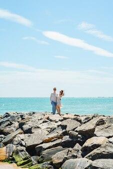 연인의 젊은 부부는 돌에 흰 옷을 입은 바다에있는 남자와 여자