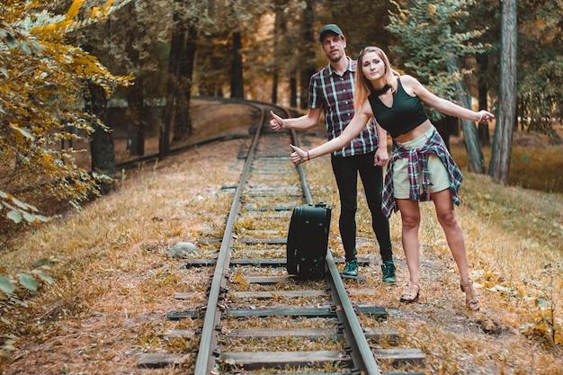 연인의 젊은 부부는 가을 숲의 레일에 기차 히치하이커를 놓쳤다