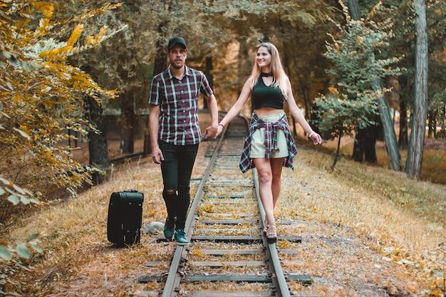기차를 놓친 젊은 연인 가을 숲의 레일 위를 걷다