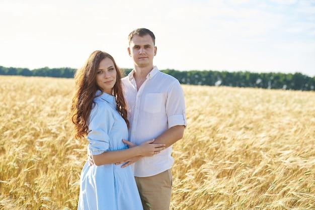Молодая пара влюбленных женщин и мужчин обнимаются на природе, в желтом пшеничном поле. понятие любви, хороших отношений, взаимопонимания и гармонии.