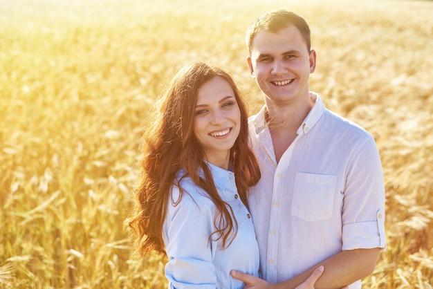 愛好家の若いカップルの女性と男性は、黄色い麦畑で、自然の中で抱擁します。愛の概念