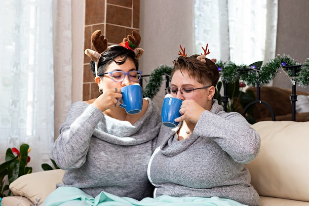 クリスマスにホットチョコレートを飲むソファに座っている2人の女性の若いカップル