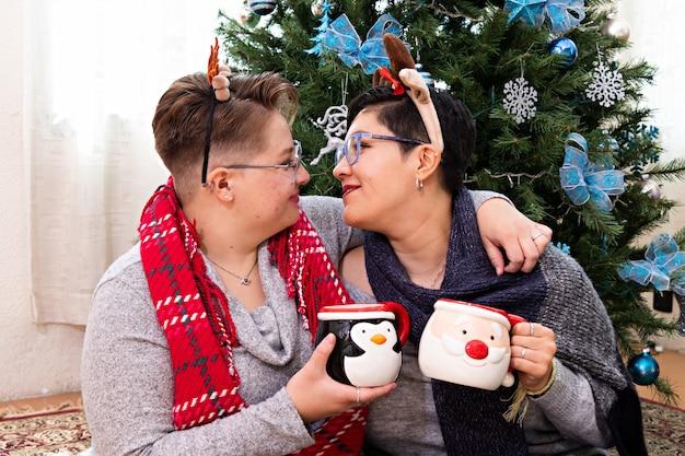 ホットチョコレートを飲むクリスマスツリーの前に座っている2人の女性の若いカップル